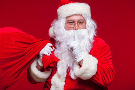 christmastime: Portrait of Santa Claus with huge red sack keeping forefinger by his mouth and looking at camera Stock Photo