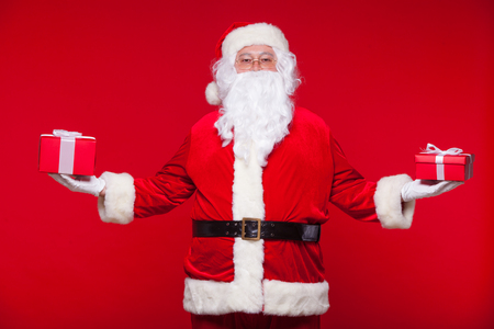 xmass: Christmas. Photo Santa Claus giving xmas present and looking at camera, on a red background