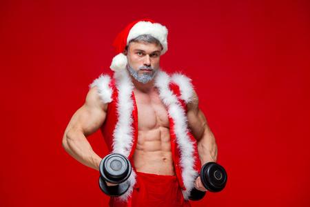 enano: Fiestas y celebraciones, año nuevo, Navidad, deportes, culturismo, estilo de vida saludable - Muscular guapo sexy Santa Claus.Isolated sobre fondo rojo. Foto de archivo