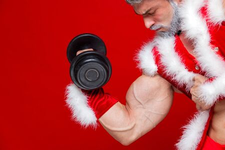 pere noel sexy: Holidays and celebrations, New year, Christmas, sports, bodybuilding, healthy lifestyle - Muscular handsome sexy Santa Claus.Isolated on red background. Banque d'images