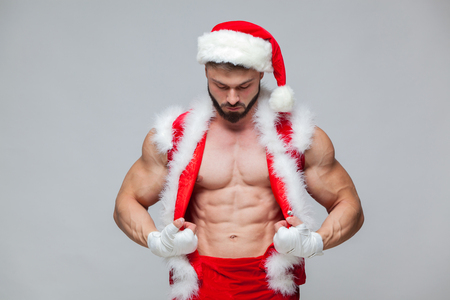 Christmas. Sexy Santa Claus . Young muscular man wearing Santa Claus hat demonstrate his muscles. Muscular Fighter kickbox With white Bandages.