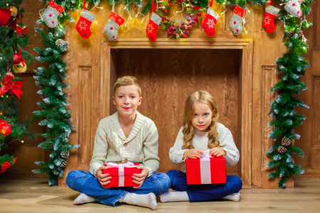 Portrait of happy children with presents around the Christmas tr Stock Photo