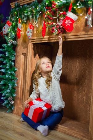 Vrolijk Kerstmis gelukkig meisje met magische gift thuis dichtbij Christma