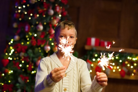 child having fun at a New Years celebration, holding sparklers
