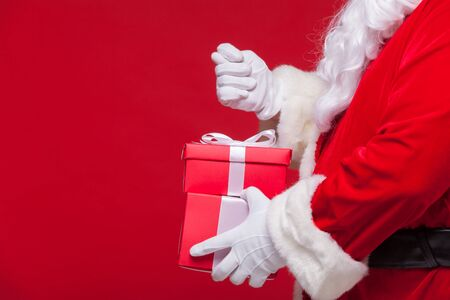 christmas Photo of Santa Claus gloved hand with red giftbox. no fig