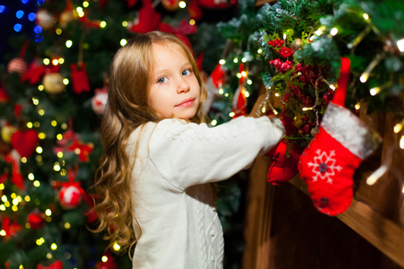 Cute toddler girl checking her Christmas stocking under a beauti Stock Photo