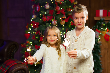 children having fun at a New Years celebration, holding sparkle Stock Photo
