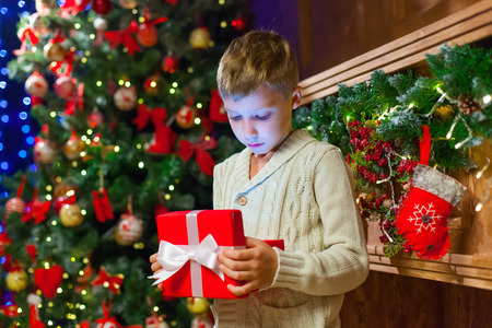 boy with Christmas gift Opening Christmas Present In Front Of Tr Stock Photo