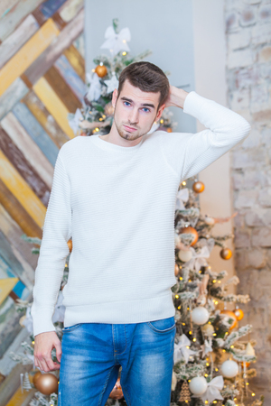 크리스마스 개념, 남성 패션입니다. 고급스러운 아파트에서 포즈를 우아한 pullover 잘 생긴 젊은 남자가 크리스마스 장식. 헤어 스타일. 스톡 콘텐츠