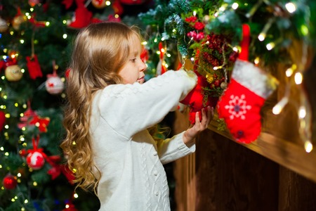 Cute toddler girl checking her Christmas stocking under a beautiful tree
