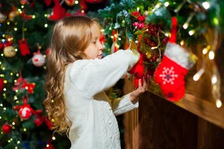 Leuk peutermeisje die haar Kerstmiskous controleren onder een mooie boom