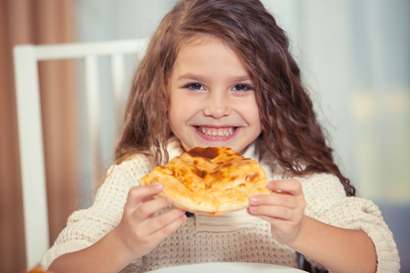 A girl in a white jacket is eating pizza at home, smiling, cake
