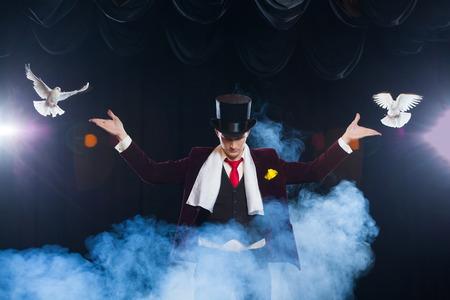 Der Zauberer mit zwei fliegenden weißen Tauben. auf einem schwarzen Hintergrund in einem schönen mysteriösen Rauch gehüllt