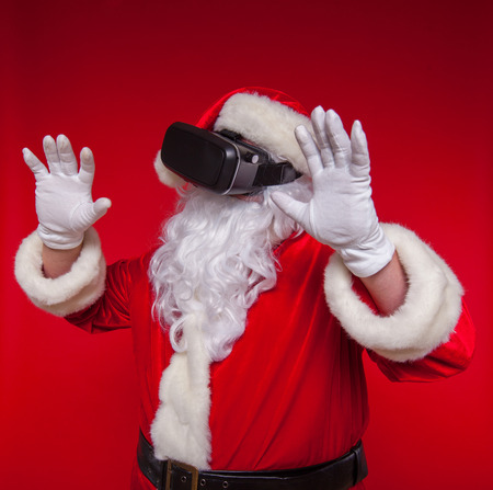 Santa Claus wearing virtual reality goggles, on a red background. Christmas Stock Photo