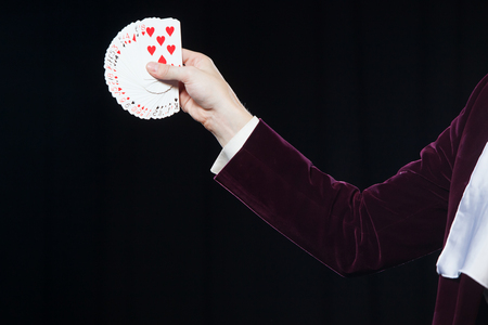 Hand with cards close-up. Midsection of magician showing fanned out cards against black background. Magician, Juggler man, Funny person, Black magic, Illusion Stock Photo