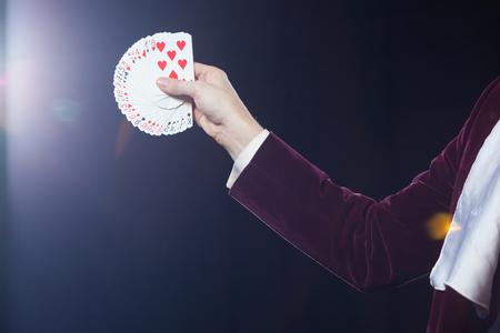 クローズ アップ カードと手。黒の背景にカードを示す手品師の中央部が煽られます。魔術師、手品師の人、面白い人、ブラック マジック、イリュ