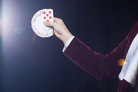 Hand with cards close-up. Midsection of magician showing fanned out cards against black background. Magician, Juggler man, Funny person, Black magic, Illusion Stockfoto