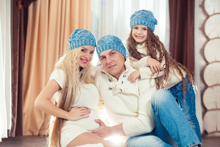 Young family sitting on floor. in a winter sweater and hat, the concept of Christmas. pregnancy in a wooden house Stock Photo