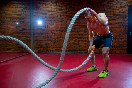 Muscular Shirtless Man in a Gym Exercises with Battle Ropes During His Fitness Workout High-Intensity Interval Training. Banco de Imagens