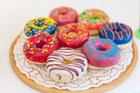 Picture of assorted donuts in a box with chocolate frosted, pink glazed and sprinkles donuts 스톡 콘텐츠
