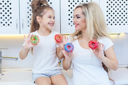 Grappige familie op de achtergrond van lichte keuken. Moeder en haar dochter meisje hebben plezier met kleurrijke donuts. Op dieet zijn concept en junkfood. Gele, roze en rode kleuren Stockfoto