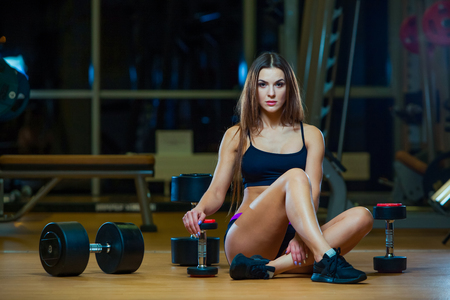 Young woman relaxing after doing pushups, woman exercising on fitness mat with dumbbells in gym. Foto de archivo