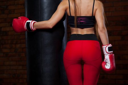 Young sexy woman with a punching bag in a gym