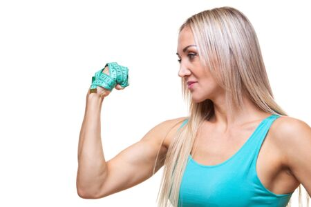 Athletic slender woman holding a measuring tape in the fist of her hand. The concept of will power, purposefulness.