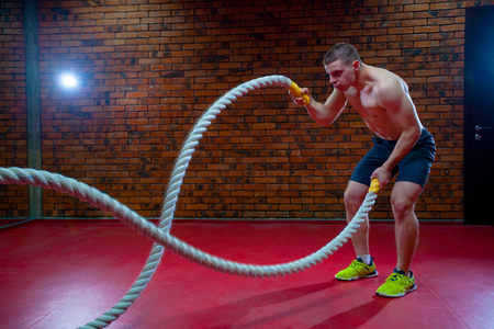 Muscular Shirtless Man in a Gym Exercises with Battle Ropes During His Fitness Workout High-Intensity Interval Training. Imagens