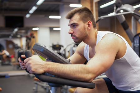 Fitness man on bicycle doing spinning at gym. Fit young man working out on gym bike.