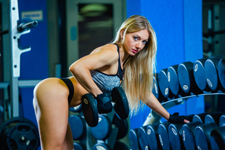 Young sexy woman doing exercises with dumbbell in gym. Classic bodybuilding. Muscular blonde fitness woman doing exercises in the gym. Fitness woman in the gym. Bodybuilder woman in the gym. Fitness woman with dumbbell. Stockfoto