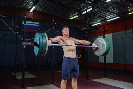 Muscular fitness man preparing to deadlift a barbell over his head in modern fitness center.Functional training.Snatch exercise.