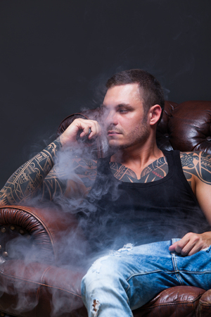 Vaper. The man with tattoos sits on a leather sofa smoke an electronic cigarette on the dark background. Stock Photo