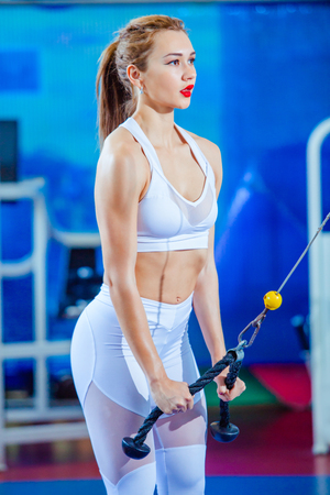 fitness woman doing triceps exercises in the crossover in the gym. Fitness girl in white sport wear with perfect body in gym exercising