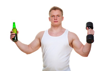 Fat man with a bottle of beer holds dumbbells isolated on white. The concept of choosing between harmful food and a healthy lifestyle. Portrait of overweight person who spoiled healthy meal . Junk meal leads to obesity. Disruption from diet concept. He is trying to go on a diet