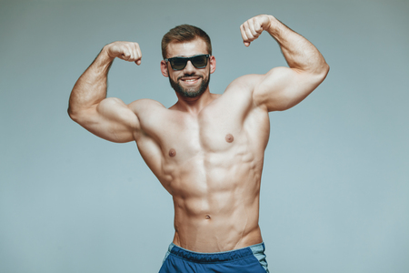 .bodybuilder posing. Beautiful sporty guy male power. Fitness muscled in blue shorts and sunglasses. on isolated grey background. Man with muscular torso. Strong Athletic Man Fitness Model Torso showing six pack abs. Archivio Fotografico