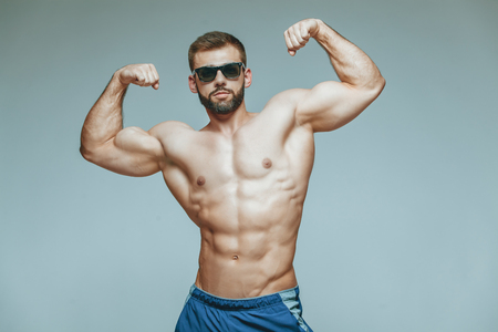 .bodybuilder posing. Beautiful sporty guy male power. Fitness muscled in blue shorts and sunglasses. on isolated grey background.