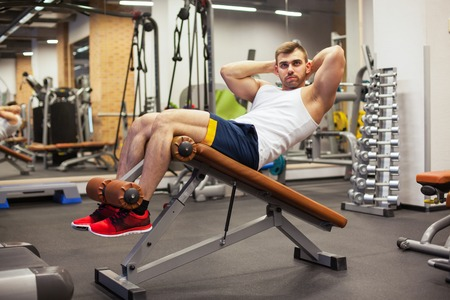 sport, fitness, bodybuilding, lifestyle and people concept - young man doing sit-up abdominal exercises Bench Press in gym Reklamní fotografie