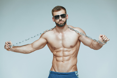 .bodybuilder posing. Beautiful sporty guy male power. Fitness muscled in blue shorts and sunglasses. on isolated grey background. Man with muscular torso. Strong Athletic Man Fitness Model Torso showing six pack abs. with chain in hands