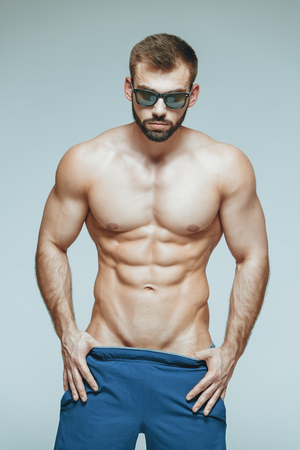 .bodybuilder posing. Beautiful sporty guy male power. Fitness muscled in blue shorts and sunglasses. on isolated grey background. Man with muscular torso. Strong Athletic Man Fitness Model Torso showing six pack abs. Stock Photo