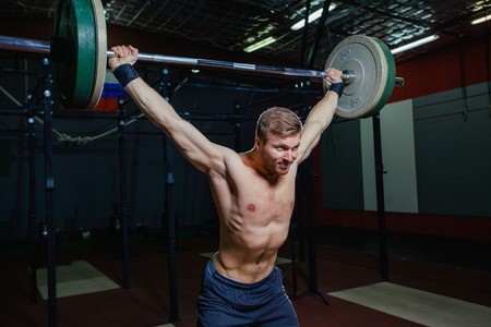 Portrait of a handsome athlete . Athlete raises the barbell over your head. shots in the dark tone. Cross style fit, deadlift