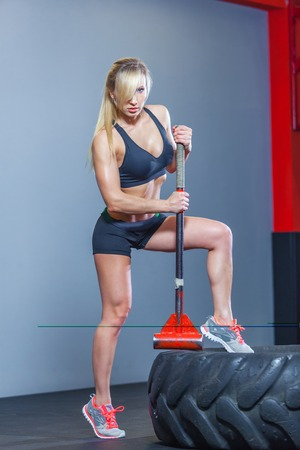 Fitness woman hitting wheel tire with hammer sledge in the gym.
