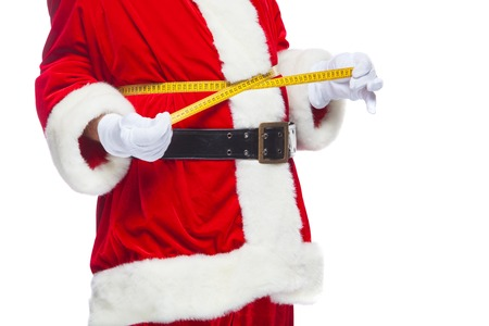 Christmas. Santa Claus is measuring waist with a tape. The concept of weight loss, healthy eating. Isolated on white background.