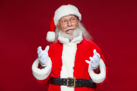 Christmas. Good Santa Claus in white gloves shows faces, grimaces, shows his tongue. Not standard behavior. Isolated on red background. 免版税图像
