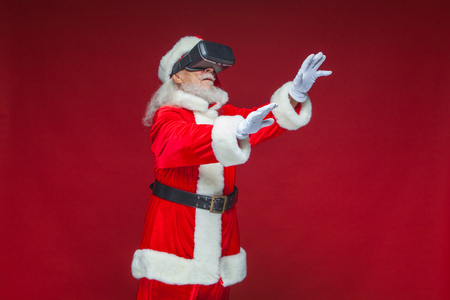 Christmas. Santa Claus in black virtual reality glasses makes gestures with his hands. Surprise, emotion. New technology. Isolated on red background. 免版税图像