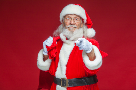 Christmas. Smiling Santa Claus in white gloves with a bag of gifts behind him points his index finger into the camera. Isolated on red background.