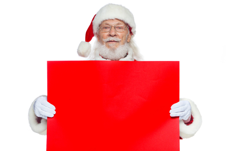 Christmas. The kind Santa Claus in white gloves holds an empty cardboard of red color. Place for advertising, for text, empty space. Copy-paste. Isolated on white background. Imagens