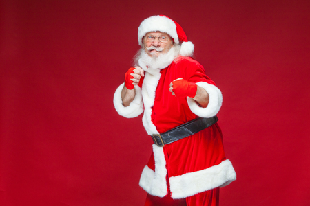 Christmas. Santa Claus with red bandages wound on his hands for boxing imitates kicks. Kickboxing, karate, boxing. Isolated on red background. Reklamní fotografie