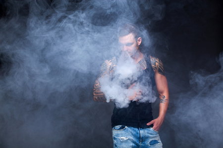 Vaper. The man with a muscular torso with tattoos smoke an electronic cigarette on the dark background