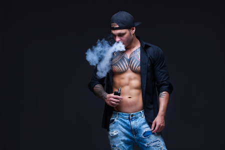 Vaper. The man dressed blue jeans, black shirt and black baseball cap with tattoos smoke an electronic cigarette on the dark background